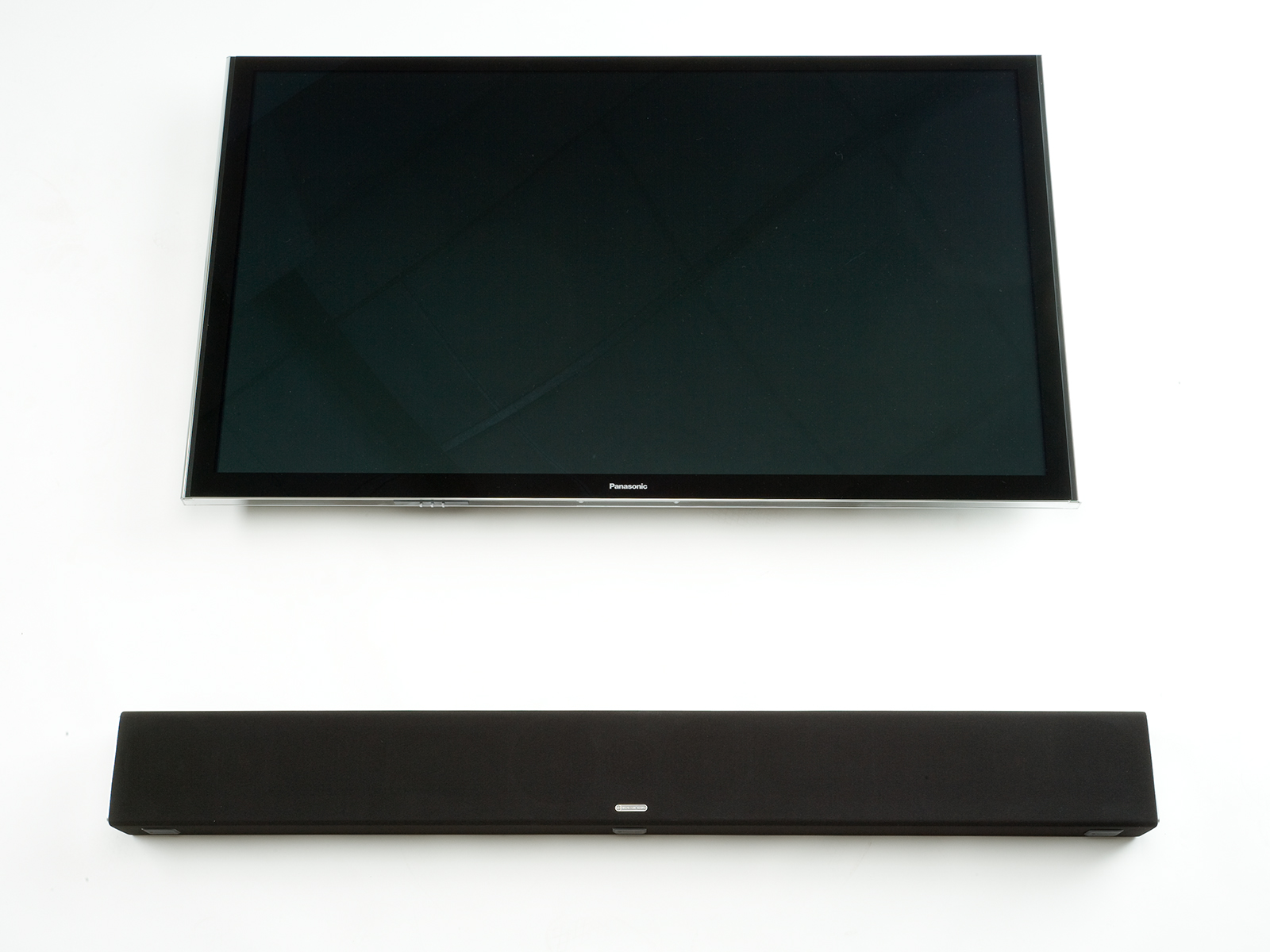 SB-3, passive soundbar speaker, with TV on a black cloth grille.